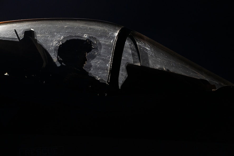An F-35A Lightning II fighter jet pilot sits in the cockpit of an F-35A at night.