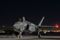 An F-35A Lightning II fighter jet prepares for take-off at night.