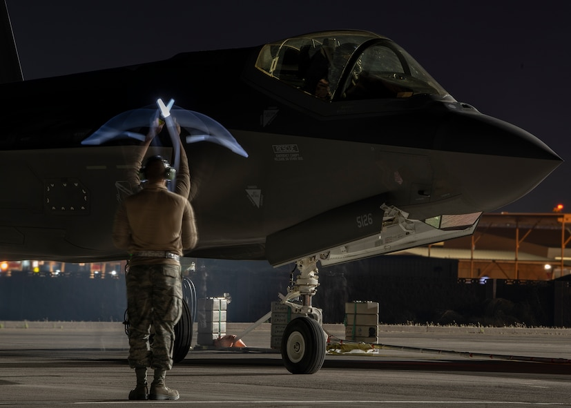 An Airman signals an F-35A Lightning II fighter jet pilot at night.