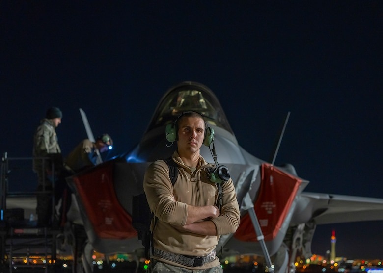 An Airman stands in front of an F-35A Lightning II fighter jet at night.