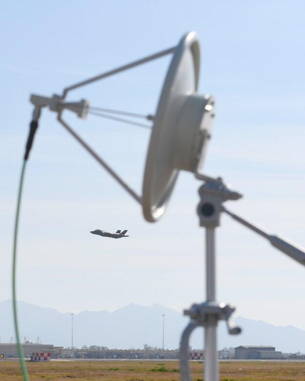 An F-35A Lightning II flies by a prototype threat emitter Jan. 17, 2020, at Luke Air Force Base, Ariz.