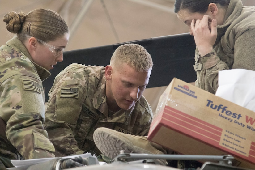 Cpl. Molly Campbell and Cpl. Caleb Creech, UH-60 helicopter repairers, 1107th Theater Aviation Sustainment Maintenance Group, work together to repair a UH-60 helicopter at Camp Buehring, Kuwait, Feb. 11, 2020.