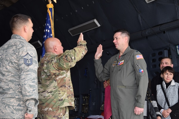 Lt. Col. John E. Sebesta, 68th Airlift Squadron C-5 pilot, administers the reenlistment oath to Tech. Sgt. Jorge Aradillas, 433rd Aircraft Maintenance Squadron ground equipment technician at Joint Base San Antonio Lackland, Texas in a C-5M Super Galaxy Feb. 15, 2020, at the Stars and Stripes Air Show in Laredo, Texas. (U.S. Air Force photo by Tech. Sgt. Iram Carmona)