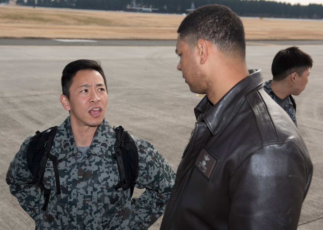 A member of the Japan Air Self-Defense Force talks with Master Sgt. Napoleon Ortiz, 374th Operations Group group evaluator loadmaster, during a tour of a C-130J Super Hercules at Yokota Air Base, Japan, Feb.12, 2020.