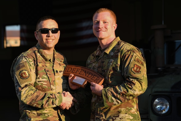 U.S. Air Force Lt. Col. Jesse Goens, 31st Security Forces Squadron commander, presents Aviano's 2020 Defender Challenge award to U.S. Air Force Airman 1st Class Hunter B. Hendrix, 31st SFS member, at Aviano Air Base, Italy, Feb. 14, 2020. Hendrix won second place. (U.S. Air Force photo by Airman 1st Class Ericka A. Woolever)