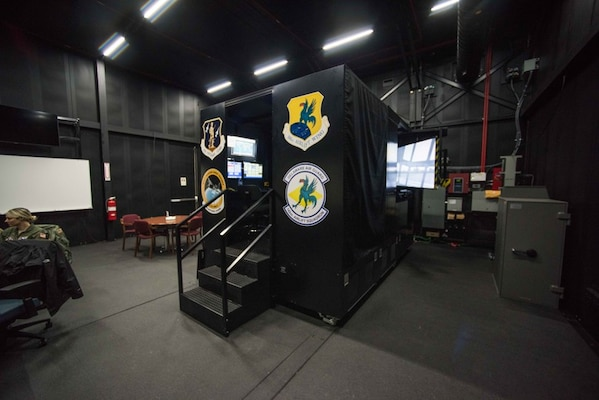 The 166th Airlift Wing C-130H2 flight simulator in its dedicated, climate controlled building, Dec. 12, 2019. The sim building also functions as a classroom and has whiteboards, presentation A/V equipment and a conference table for crew training.