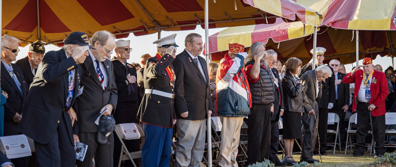 Iwo Jima veterans, along with more than 100 others in attendance, stand and salute during the national anthem at the 75th Commemoration of the Battle of Iwo Jima sunset ceremony at Marine Corps Base Camp Pendleton, California, Feb. 15.