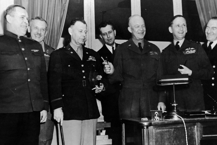 A group of military officials stand together with one of them holding a pen.