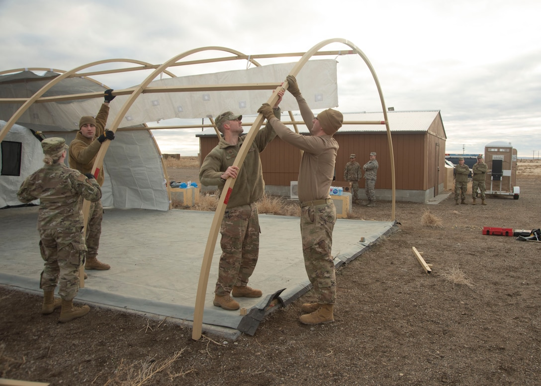 U.S. Air Force 2nd Lt. Doug Jaks, 366th Civil Engineering Squadron chief of operations, assists a group of Airmen in connecting aluminum arches, Jan. 23, 2020, on Mountain Home Air Force Base, Idaho. This training prepares Airmen for obstacles in future deployments. (U.S. Air Force photo by Airman 1st Class Akeem K. Campbell)