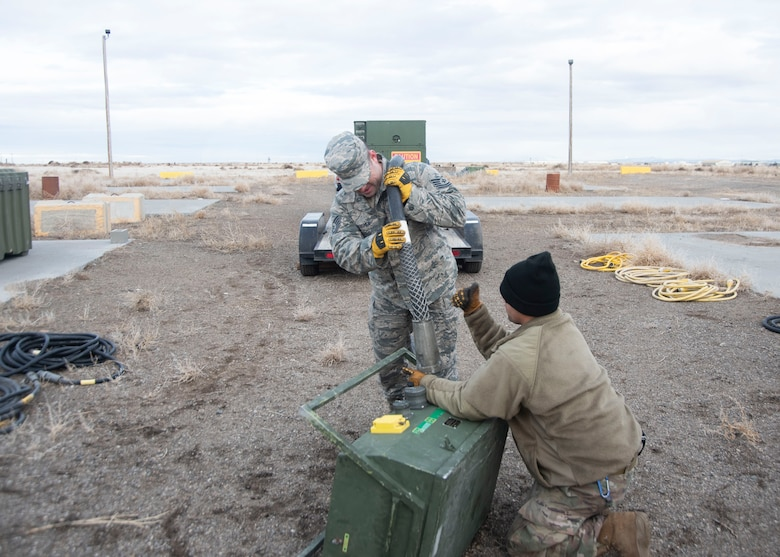 U.S. Air Force Tech. Sgt. Chris Archer, 366th Civil Engineering Squadron power production craftsman, assists Staff Sgt. Kevin Rivera Calzada, 366th Civil Engineering Squadron power production journeyman in setting up a remote power source, Jan. 23, 2020, on Mountain Home Air Force Base, Idaho. This is part of the structural build-up of the Base Emergency Engineer Force training which produces multicapable Airmen. (U.S. Air Force photo by Airman 1st Class Akeem K. Campbell)