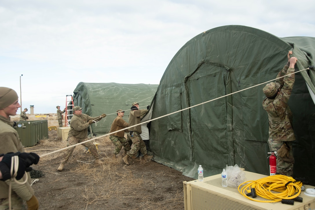 A group of U.S. Air Force Airmen secure a tent cover, Jan. 23, 2020, on Mountain Home Air Force Base, Idaho. This training was conducted to equip Airmen with skills from other career fields to enhance their readiness and multi-functionality. (U.S. Air Force photo by Airman 1st Class Akeem K. Campbell)