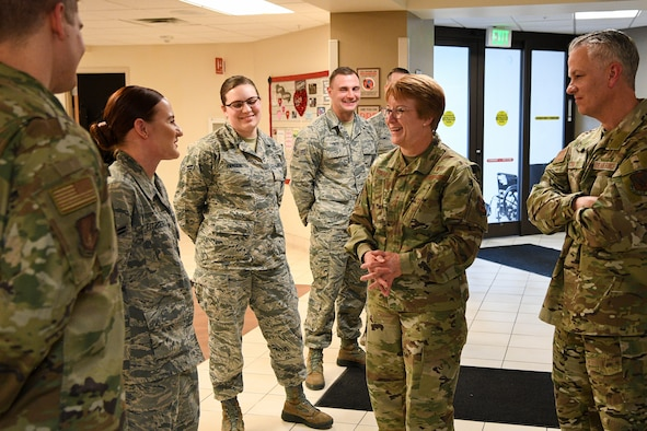 Lt. Gen. Hogg (center) talks with Airman 1st Class Sofia Fitzgerald (left) in the lobby of the medical clinic while others watch on.