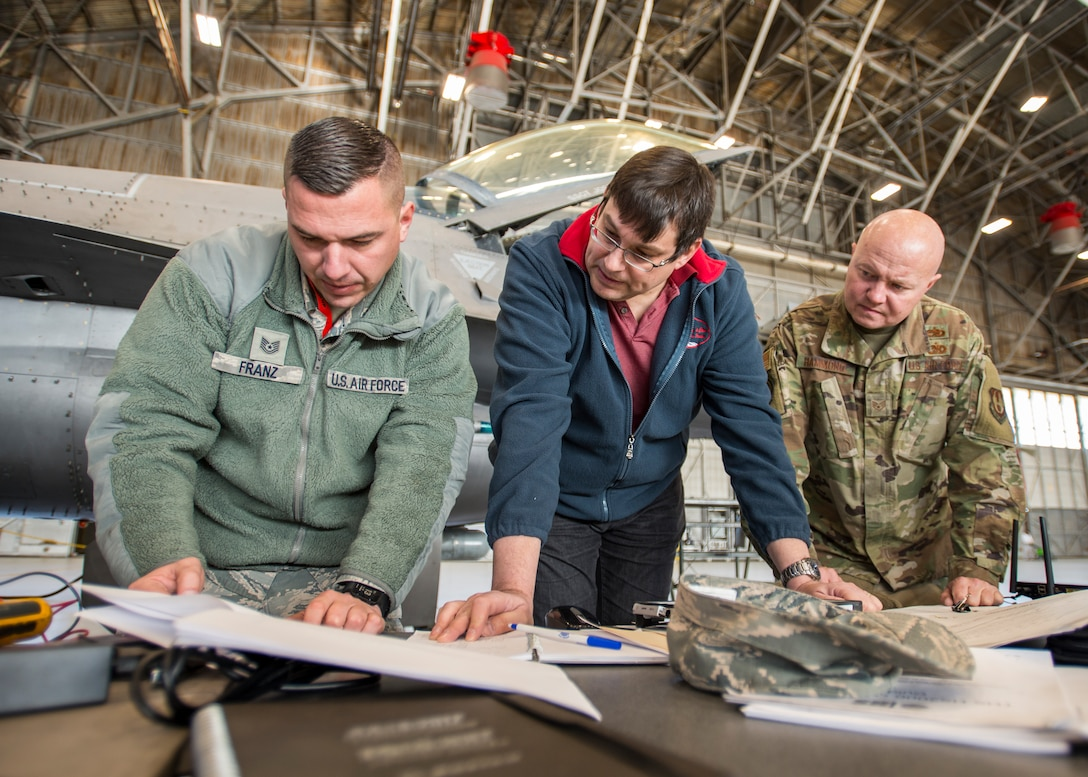Tech. Sgt. Alex Franz, 412th Aircraft Maintenance Squadron, Martin Leduc, Technologies Harness Scanner engineer, and Staff Sgt. Jocko Hammond, 412th AMXS, review F-16 electrical wiring schematics during an Advanced Mobile Universal Electrical Tester, or AMUET, testing session at Edwards Air Force Base, California, Feb. 4. (Photo by Giancarlo Casem)