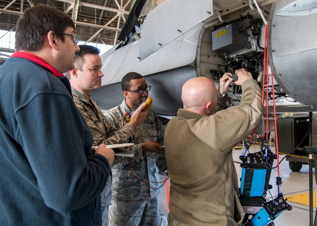 Martin Leduc, Technologies Harness Scanner engineer, Tech. Sgt. Charles Prince, 412th Logistics Test Squadron, Staff Sgt. Marcell Pemberton, 412th MXLS, and Staff Sgt. Jocko Hammond, 412th Aircraft Maintenance Squadron, gather baseline readings from an F-16 avionics wire bundle using a hand-held multi-meter at Edwards Air Force Base, California, Feb. 4. (Photo by Giancarlo Casem)