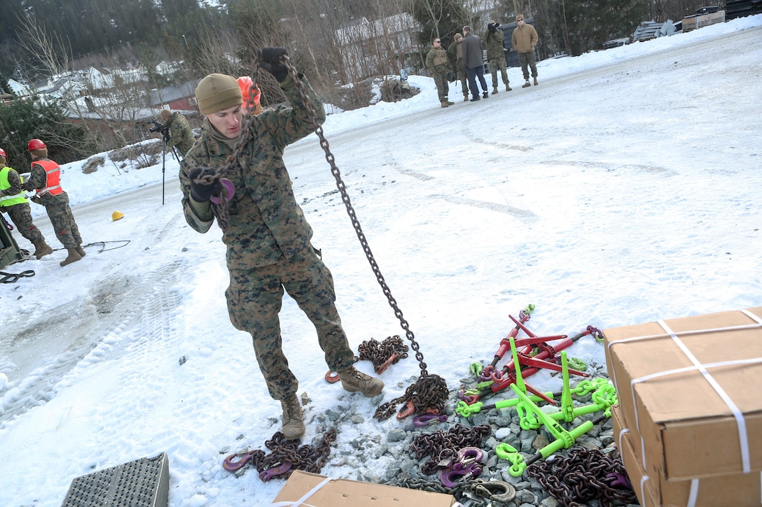 A Marine stands in the snow. He holds his left hand above his head, and a chain dangles from his hand.