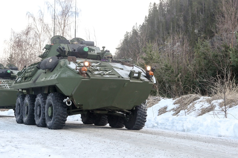 A military vehicle heads down a snow-covered road.