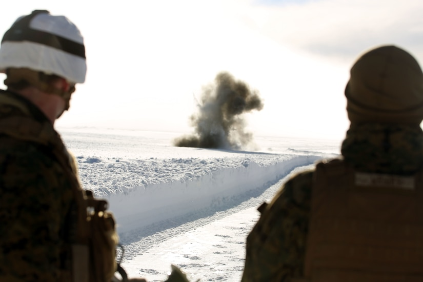 A cloud blooms out of a snowfield. Two service members watch.