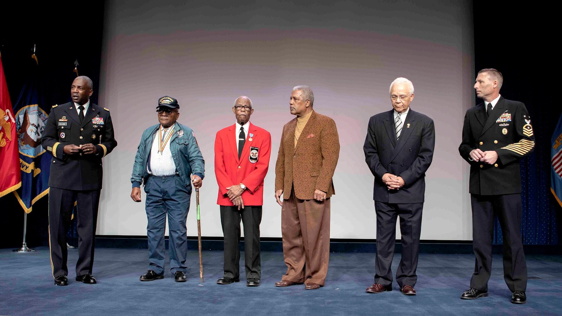 Six men stand on a stage. Man on the far left and far right are in military dress uniform.
