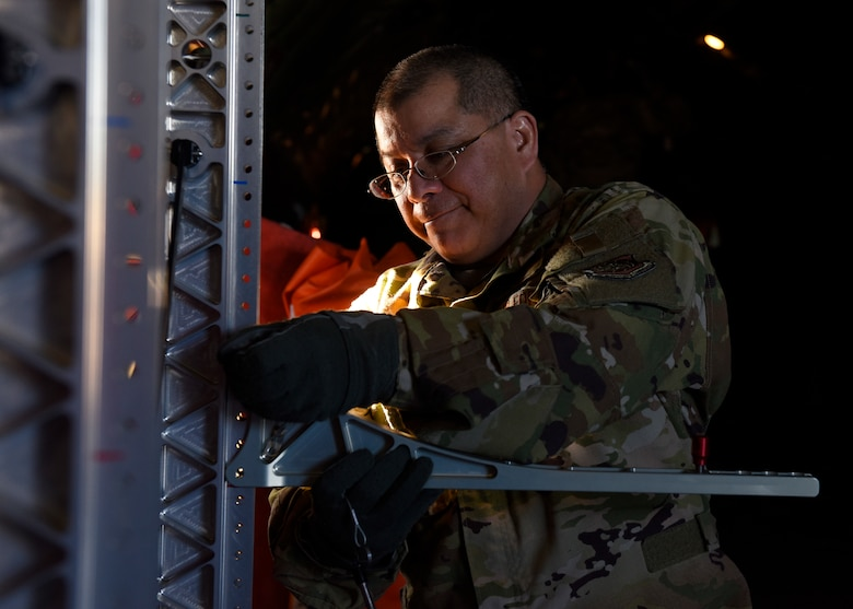 U.S. Air Force Lt. Col. David Hernandez, 43rd Aeromedical Evacuation Squadron chief flight nurse, prepares a litter stanchion system on a Fairchild Air Force Base KC-135 Stratotanker prior to an aeromedical evacuation mission at Travis Air Force Base, California, Feb. 11, 2020. Training consisted of familiarization of the KC-135 airframe for emergency evacuation procedures, in-flight medical emergency simulations, aircraft emergency simulations and how-to best organize medical equipment for both Fairchild and Travis Airmen in order to qualify for semi-annual requirements. (U.S. Air Force photo by Senior Airman Lawrence Sena)