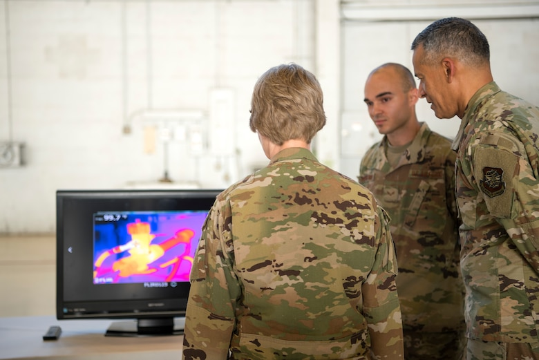 """U.S. Air Force Gen. Maryanne Miller, Air Mobility Command commander, and Chief Master Sgt. Terrence Greene, AMC command chief, are briefed on the use of thermal imaging to detect faults in the aircraft at MacDill Air Force Base, Fla., Feb. 13, 2020. Thermal imaging cameras were recently implemented as part of the wing's """"Fuel Tank"""" program, which gives Airmen the opportunity to present innovative ideas to leadership."""