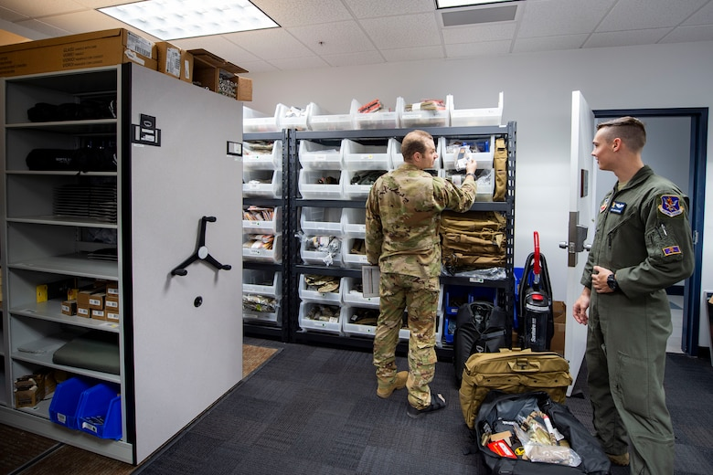 Photo of an Airman showing another Airman equipment.