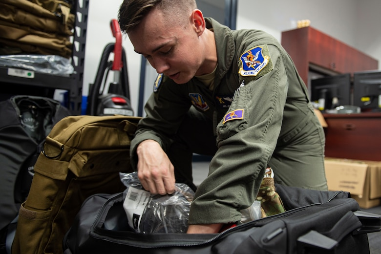 Photo of an Airman packing issued equipment into a bag.