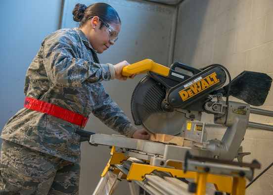 Airman Basic Starr Figueroa, 103rd Logistics Readiness Squadron traffic management specialist, operates an arm saw at Bradley Air National Guard Base, East Granby, Conn. Feb. 8, 2020. Traffic management specialists construct custom shipping containers to Air Force specifications for safe delivery of certain pieces of equipment, including C-130H wheels. (U.S. Air National Guard photo by Staff Sgt. Steven Tucker)