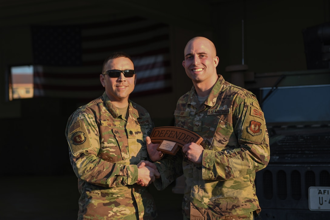 U.S. Air Force Lt. Col. Jesse Goens, 31st Security Forces Squadron commander, presents Aviano's 2020 Defender Challenge award to Senior Airman Christopher L. Ray, 31st SFS member at Aviano Air Base, Italy, Feb. 14, 2020. Ray won first place. (U.S. Air Force photo by Airman 1st Class Ericka A. Woolever)