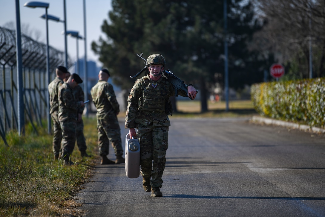 U.S. Air Force Airman 1st Class Hunter B. Hendrix, 31st Security Forces Squadron member, carries one jerry can, and an M240 machine gun at Aviano Air Base, Italy, Feb. 14, 2020. Airmen participated in a 400 meter equipment carry during the three day Defender Challenge. (U.S. Air Force photo by Airman 1st Class Ericka A. Woolever)