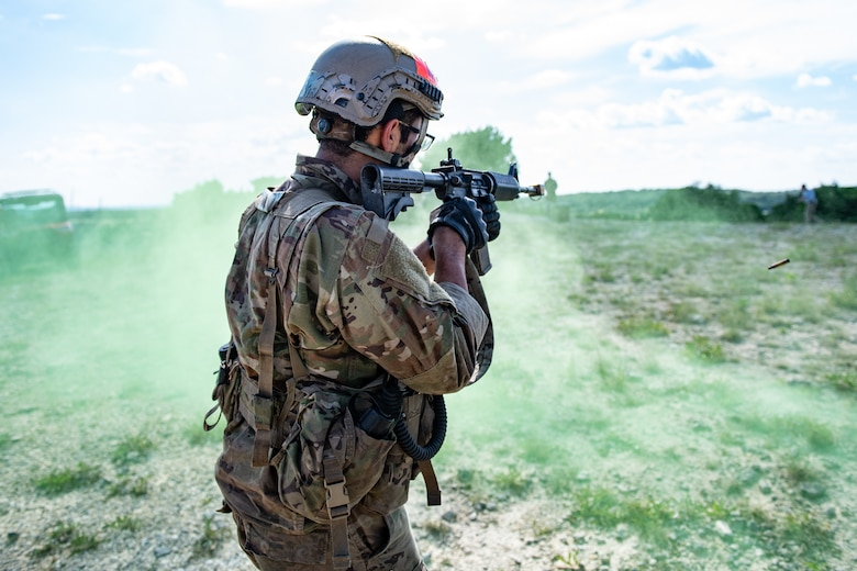 Special warfare trainee patrols in the middle of green smoke