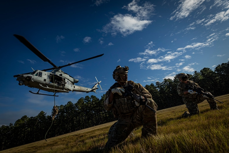 Airmen look out after fast roping to ground from helicopter