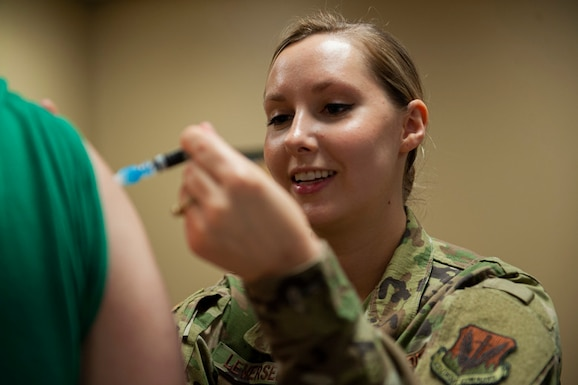 A photo of an Airman administering the flu shot