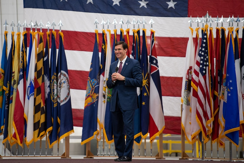 Defense Secretary Dr. Mark T. Esper speaks on a stage with flags behind him.