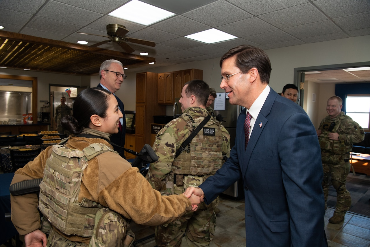 Defense Secretary Dr. Mark T. Esper shakes hands with an airman .