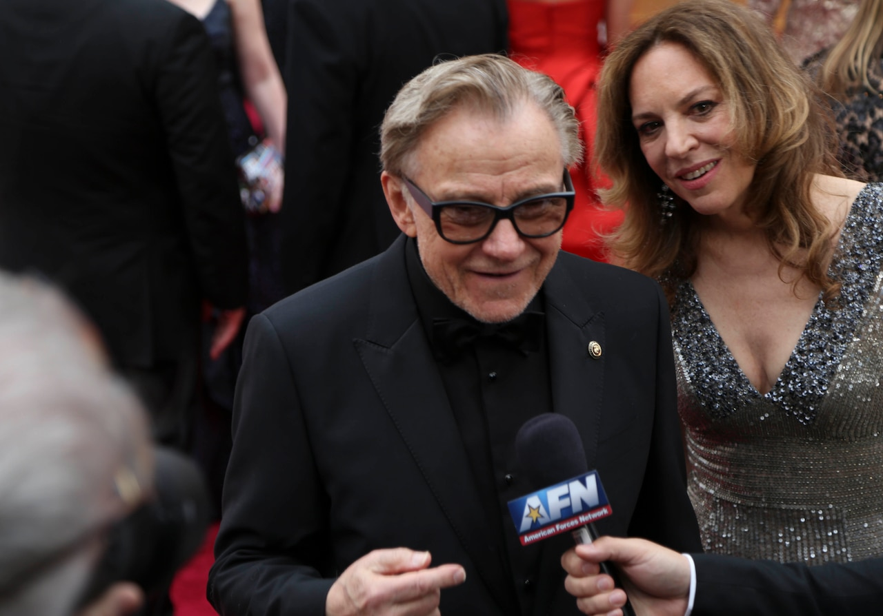 A man in a black suit wearing black-framed glasses talks to someone off-camera who's holding an AFN microphone. A woman in silver stands behind him.
