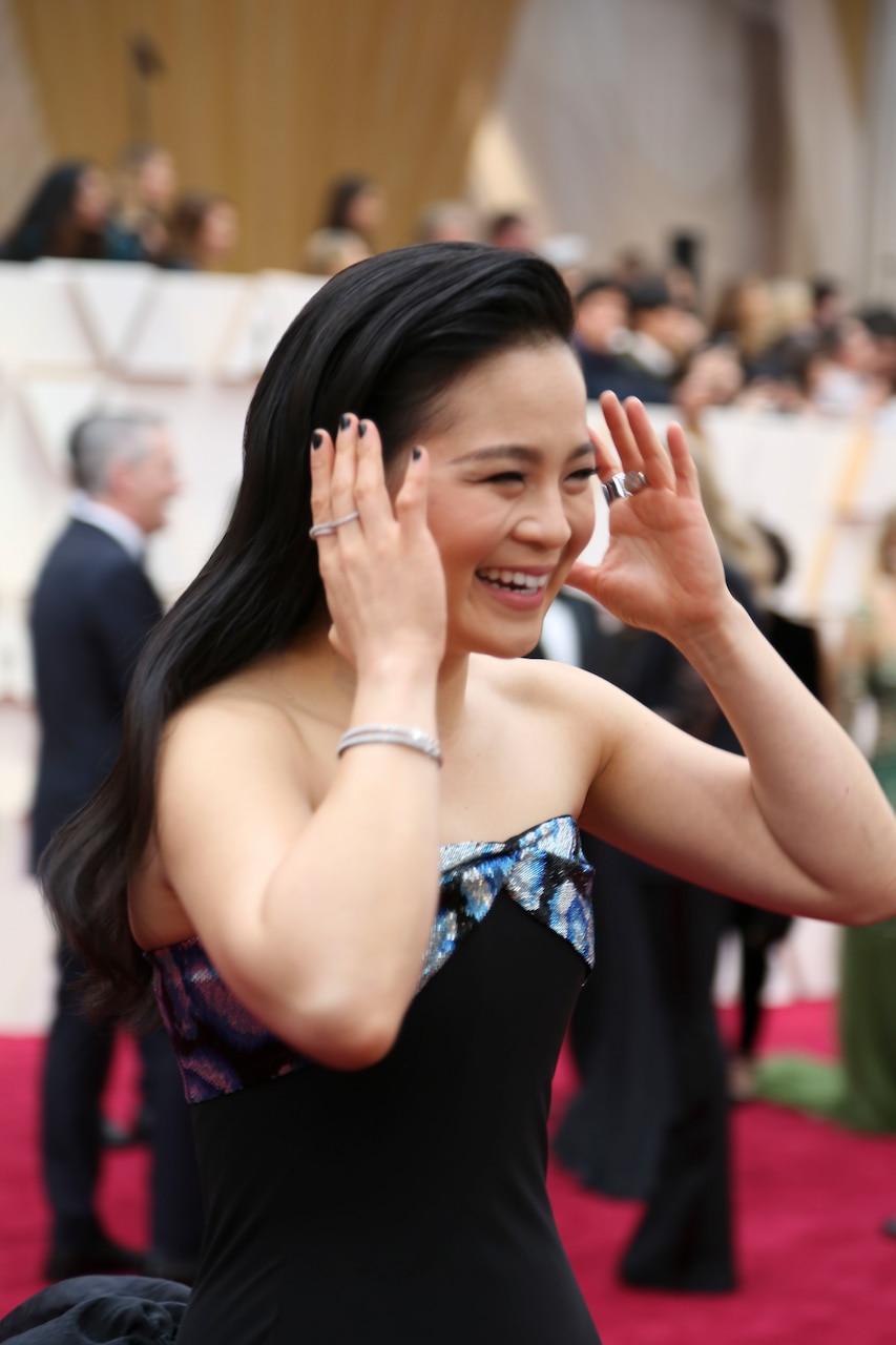 A smiling woman in a black dress holds her hands up to her head as if she's about to push her hair back.