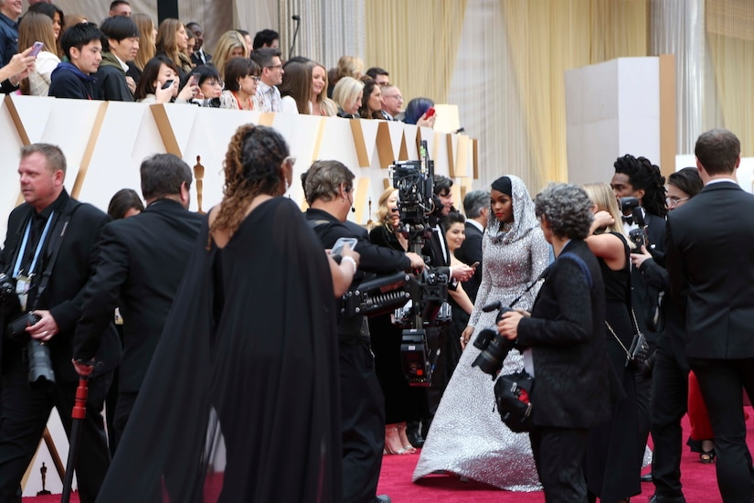 Photographers on a red carpet swarm a woman wearing a shimmering long silver gown with a matching hood on her head. Onlookers in stands above the carpet look down at her.