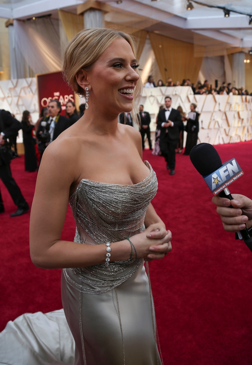 A woman in a strapless silver gown holds her hands clasped in front of her and smiles as she talks to a person off camera holding an AFN microphone.
