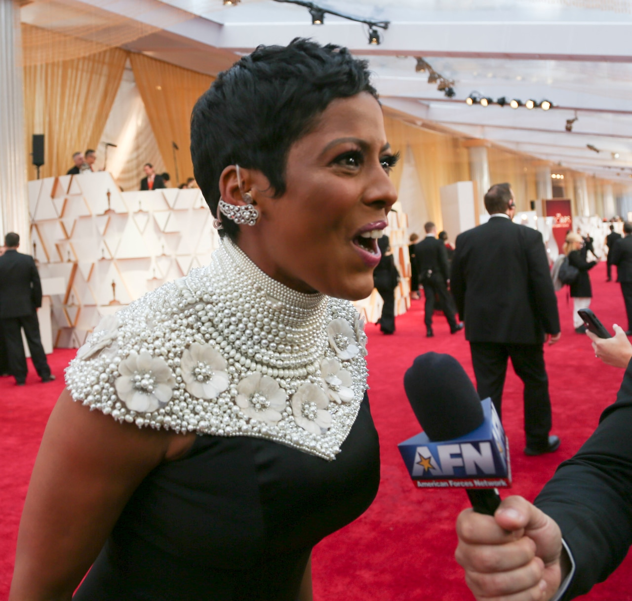 A woman in a black dress with pearl-beaded neckline talks to someone off-camera who's holding a microphone on a red carpet.