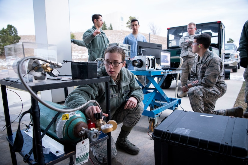 Military personnel work outdoors with equipment connected to a tiny jet engine.