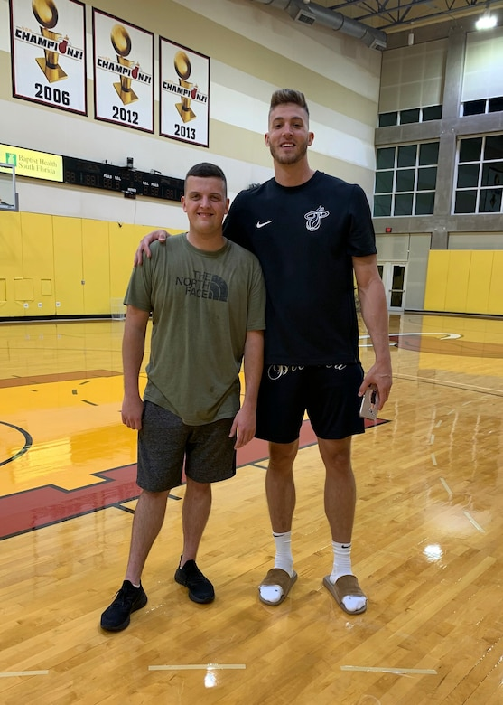 Senior Airman John Senn (left), 103rd Maintenance Squadron aerospace ground equipment maintainer, and Meyers Leonard, Miami Heat power forward, at the Miami Heat practice facility in Miami, Fla. After the two met through online gaming, Leonard helped Senn achieve his fitness goals by designing a workout and nutrition plan and checking in for weekly weigh-ins. (Courtesy photo)