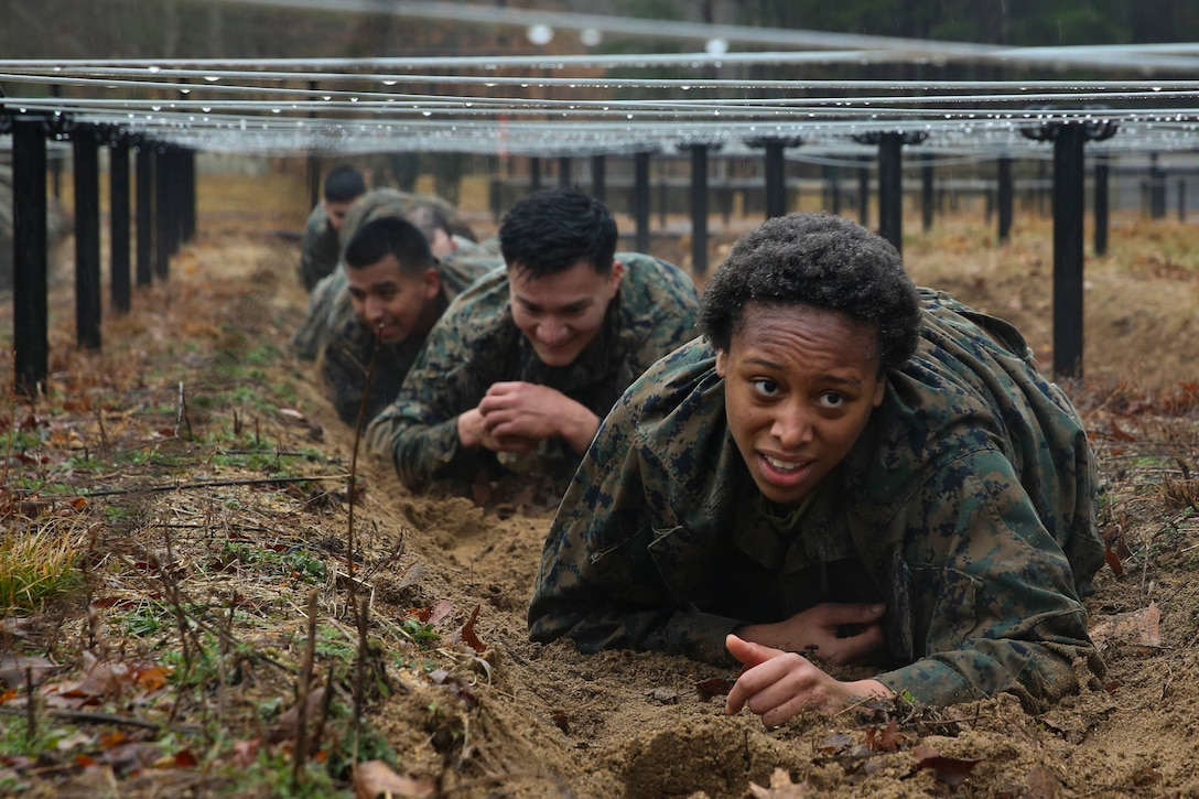A line of Marines crawl underneath barbed wire.
