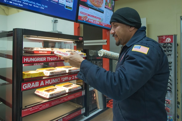 A 47th Maintenance Directorate maintainer grabs a slice of pizza Feb. 12, 2020. Hunt's Brothers Pizza, now open at the Army and Air Force Exchange Service's shopette since last Thursday, offers pizza by either the slice or the box.