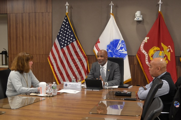 Leaders discuss Troop Support mission around the table.