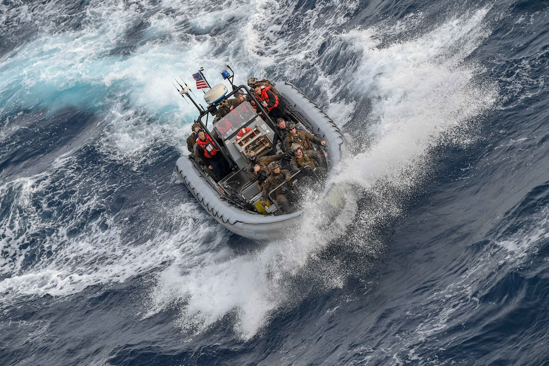 A group of sailors and Marines ride in an inflatable boat.
