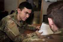Two Airmen review work orders at the 375th Logistics Readiness Squadron Vehicle Maintenance flight.