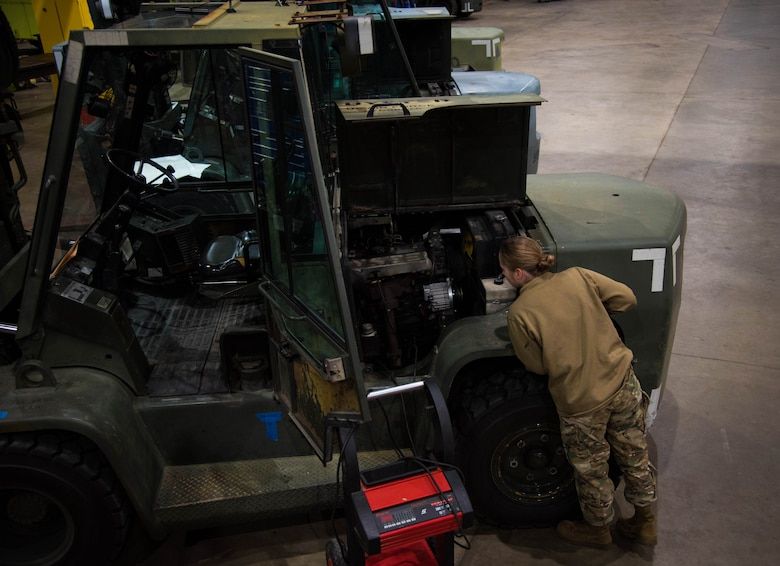 Vehicle maintainer looks at forklift.