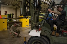 Vehicle maintainers evaluate forklift.