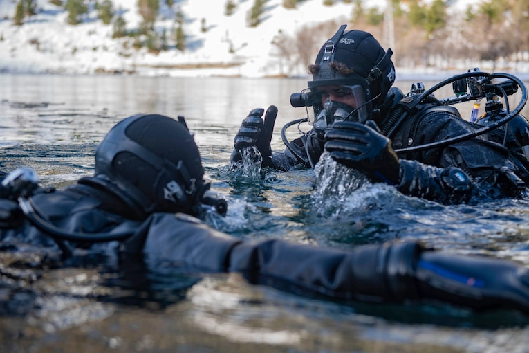 Two sailors move in water up to their shoulders.