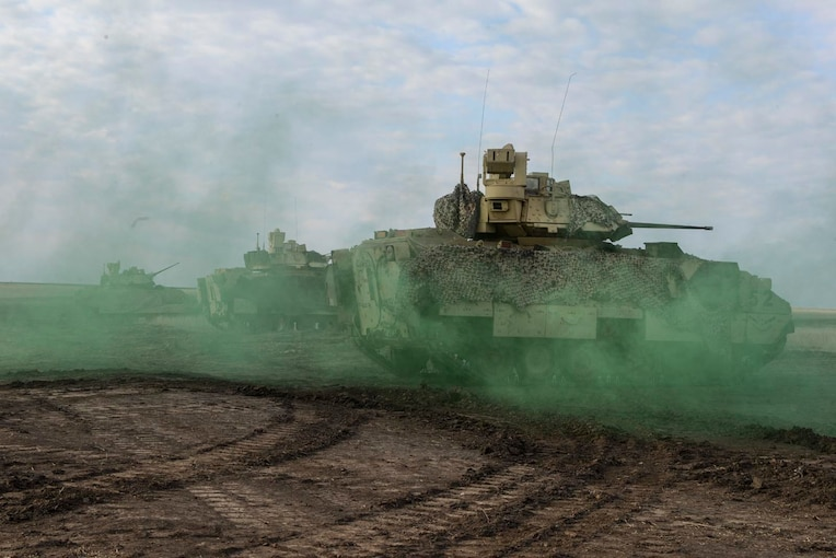 Tanks move through a dirt road surrounded by green smoke.